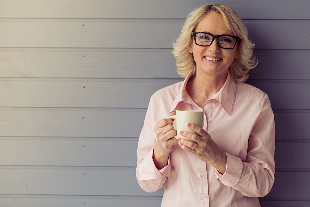 blond female smiling holding a cup of coffee