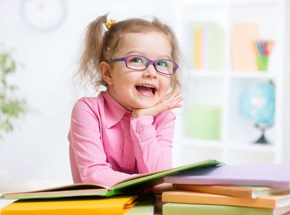 pediatric girl purple glasses resting elbow on school books